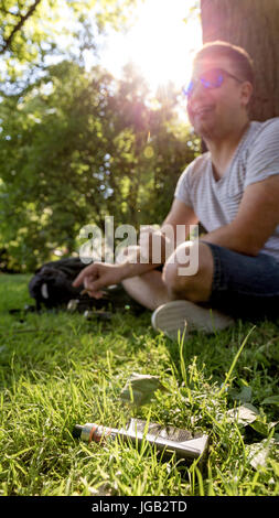 Teen male smoking tobacco cigarillo with vaporizer on foreground - Stock Image