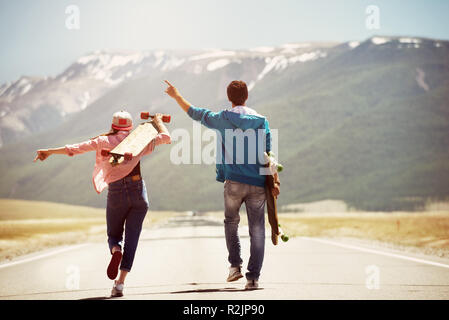 Happy couple is walking by straight road with skateboards or longboards on background of mountains - Stock Image