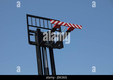 Empty Fork of a Forklift truck in front of blue sky - Stock Image