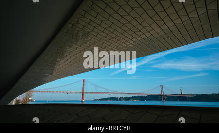 Famous MAAT Museum in Lisbon near river Tagus framed with Lisbon landmark 25 of April bridge and Rei Cristo - Stock Image