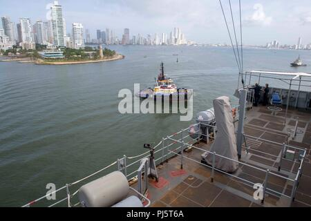 180827-N-GX781-0005 CARTAGENA, Colombia (Aug. 27, 2018) A tug boat pulls alongside the Whidbey Island-Class Dock Landing Ship USS Gunston Hall (LSD 44) as the ship pulls in to Cartagena, Colombia for a scheduled port visit. The Gunston Hall is on deployment supporting Southern Seas, which is an annual collaborative deployment in the U.S. Southern Command area of responsibility where a task group will deploy to conduct a variety of exercises and multinational exchanges to enhance interoperability, increase regional stability, and build and maintain regional relationships with countries througho - Stock Image