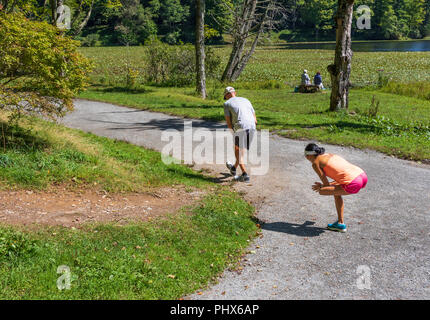 BLOWING ROCK, NC, USA-8/23/18: Two runners, male and female, stretching prior to running around Bass Lake and two women sit on a bench near the lake. - Stock Image