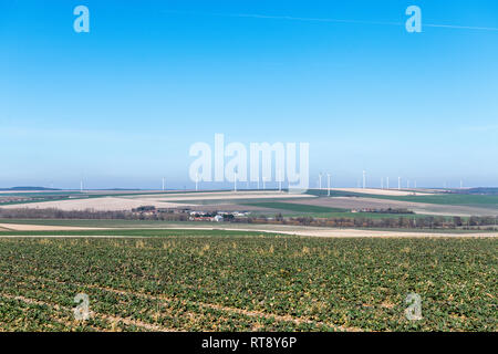 Wind turbines on a hill. Wind turbines generating electricity with blue sky energy conservation concept. - Stock Image