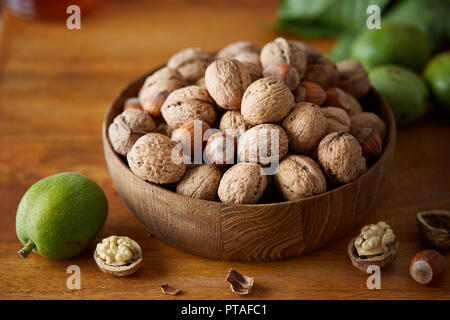 Bowl of walnuts and hazelnuts on wooden table. Fresh walnuts with and without shells on a wooden surface. - Stock Image