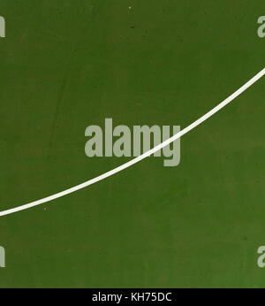 Pole aerial image of an outdoor basketball court. White line intersects green playing surface. - Stock Image