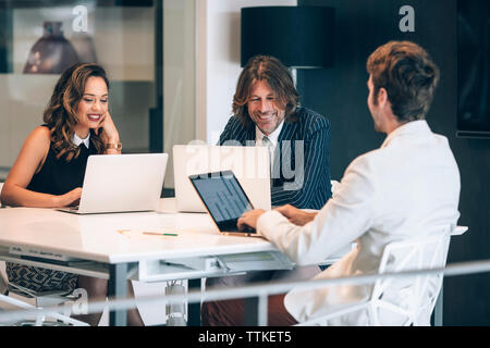 Happy business people discussing in office - Stock Image