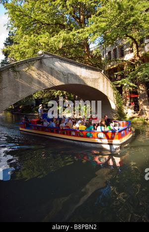 San Antonio River Walk above riverwalk tour boat with tourists passes under arched bridge crossing the San Antonio - Stock Image