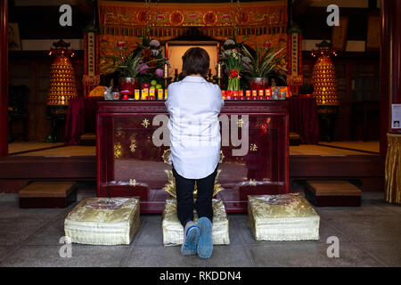 A woman kneels and prays at Pu Chi Temple, a Shingon Buddhist temple in Beitou Distirict in northern Taipei, Taiwan. - Stock Image