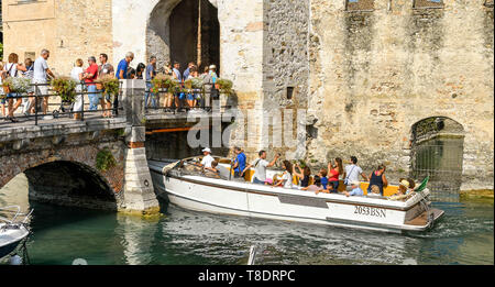 SIRMIONE, LAKE GARDA, ITALY - SEPTEMBER 2018: A sightseeing motor boat full of tourists passing under people on the bridge into Scaliger Castle in the - Stock Image