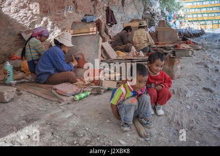 Mani stone plate carver family enroute Lingkhor kora, Lhasa, Tibet. - Stock Image