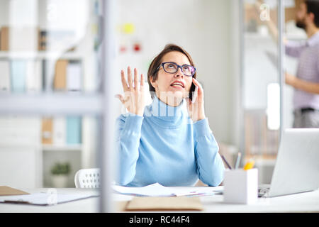 Annoyed office manager explaoinign something to client on the phone while sitting by desk in office - Stock Image
