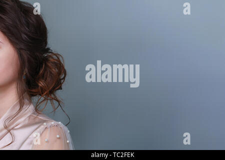 Side view of woman with long curly hair tied in knot at nape. Natural hair and color. Wedding and prom ball hairstyles. Beauty industry - Stock Image
