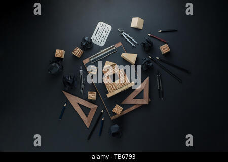 House construction, planning, and repairment concept. Wooden block home on a clipboard with engineering equipment. Working on a blueprint flat lay - Stock Image
