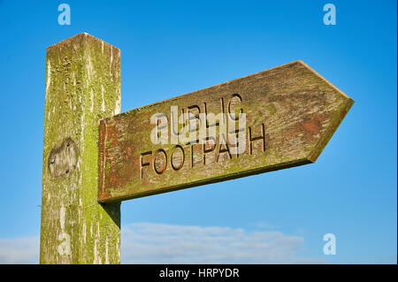 A timber fingerpost sign indicating a public footpath right of way, against a blue sky. - Stock Image