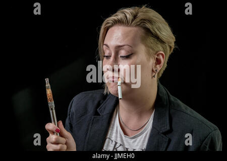 Woman looking at electronic cigarette and thinking about it - Stock Image