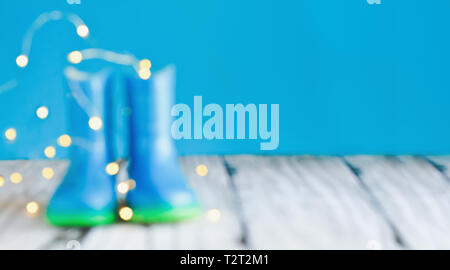 Abstract bokeh and blurred colorful background of children's rain boots / wellies with bokeh agaisnt a blue background with room for copy space. - Stock Image