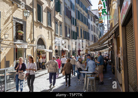 Italian city street scene in the centre of Florence, people relaxing at a bar cafe in the narrow street,Florence,Tuscany,Italy - Stock Image