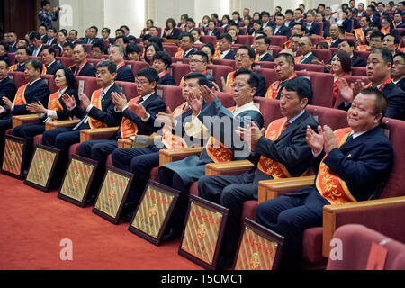 Beijing, China. 23rd Apr, 2019. Attendees applause during a conference held to highlight the contribution of 'model workers' and groups in Beijing, capital of China, April 23, 2019. China on Tuesday held a conference here to highlight the contribution of 'model workers' and groups ahead of the International Labor Day, which falls on May 1. A total of 695 individuals and more than 800 groups were honored at the event. Credit: Cai Yang/Xinhua/Alamy Live News - Stock Image
