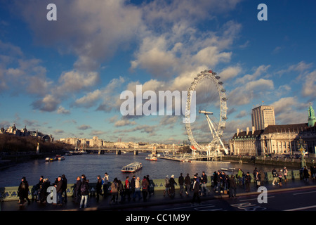 View over the River Thames, London Eye and pedestrians walking along Westminster Bridge, London, England, United - Stock Image