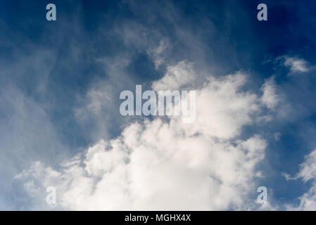 Wispy white clouds and turbulent sky taken during a winter's day with crisp blue areas of natural skyline - Stock Image