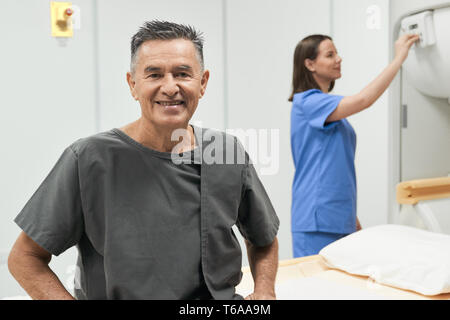 Portrait Of Happy Senior Man Smiling As Patient In Hospital - Stock Image