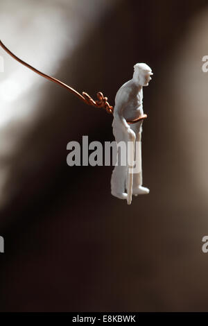 Figurine of an old man hanging in the void. - Stock Image
