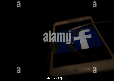 Facebook logo is shown on a smartphone display, focus view through eyes glasses - Stock Image