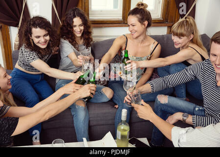 Group of male and female adult friends sitting on sofa making a toast - Stock Image