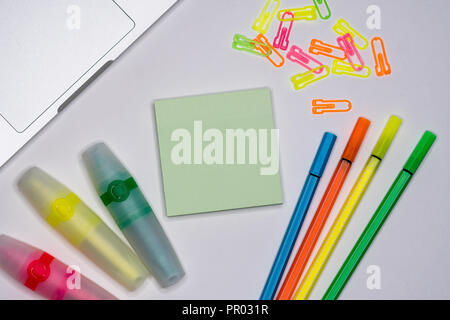 Mix of office supplies around sticky note on a table background. Copy space. View from above. - Stock Image