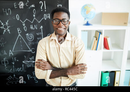 Young successful African-american teacher with arms crossed on chest standing by blackboard in classroom - Stock Image