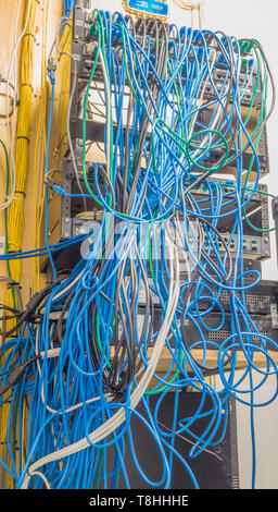 Example of poorly installed network switches with a tangled mass of patch cords and a dusty environment. - Stock Image