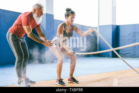 Fit woman training with battle rope inside gym - Hipster personal trainer motivating a female athlete who's doing endurance exercises - Stock Image