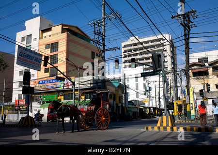 A kalesa crosses through an intersection in Manila, Philippines. - Stock Image
