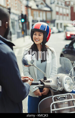 Smiling young woman in helmet on motor scooter, talking to friend on urban street - Stock Image