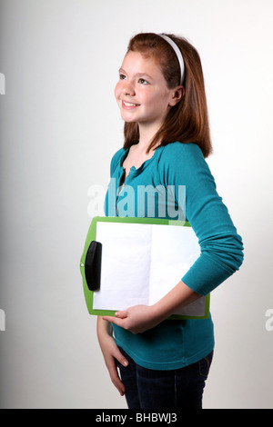 Studio shot of a girl holding a clipboard - Stock Image