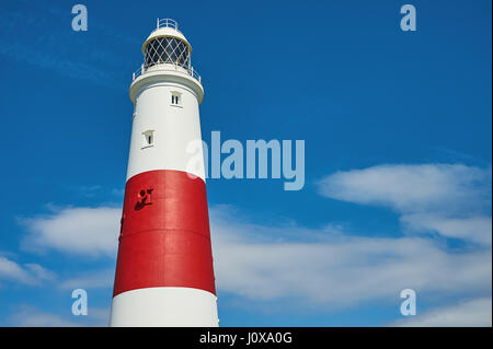 The red and white tower of Portland light house, on the southern end of Portland Bill against a blue sky. - Stock Image