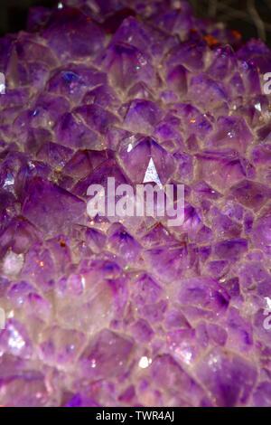 violet amethyst quartz close up view, amethyst geode natural crystal gemstone macro shot purple background with bokeh effect - Stock Image