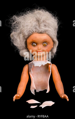 Old broken doll. Isolated on black background. Single damaged toy. Part of dirty child dolly. Gray hair and squint eyes. Plastic shards. Abuse, horror. - Stock Image
