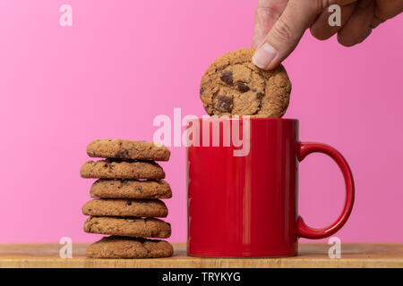 Dunking a biscuit in to a cup of coffee, chocolate chip cookies. - Stock Image
