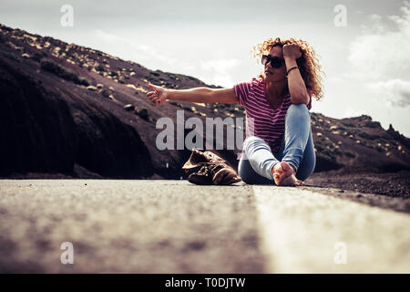 Beautiful curly caucasian woman sitting on the asphalt with broken trekking shoes waiting and asking for help to travel by car - concept of traveler a - Stock Image