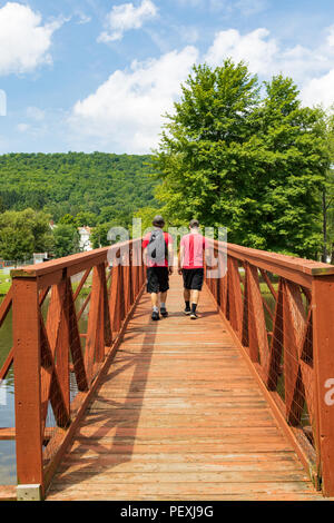 SMETHPORT, PA, USA-11 AUGUST Two boys cross the footbridge in Hamlin Park the small borough of Smethport. - Stock Image