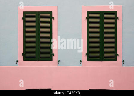 Details of old medieval style building. The building has grey concrete walls and the window frames pink and made of wood. Photographed in Nyon. - Stock Image