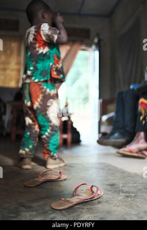 Young Africian child stands in rural house in Uganda and takes a photo using a camera with shoes on the floor - Stock Image