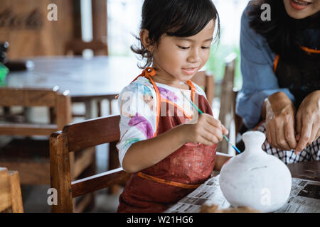 mother and daughter painting ceramic pot in pottery workshop - Stock Image
