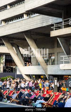 London, England, UK - May 31, 2019: A crowd of people enjoy deck chairs outside the bar of the National Theatre on London's South Bank. - Stock Image
