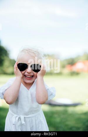 Happy girl wearing sunglasses - Stock Image