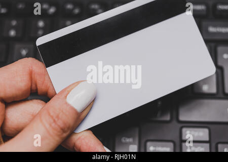 woman's hand holding payment card with laptop keyboard in the background, concept of online shopping and purchases - Stock Image