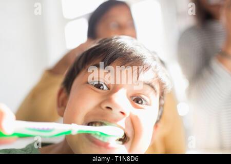 Portrait playful, silly boy brushing teeth - Stock Image