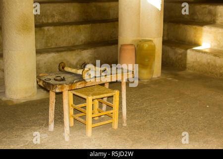 A small rough wooden table with Torah Scroll in the Synagogue in the open air museum of Nazareth Village Israel. This site provides an authentic look  - Stock Image