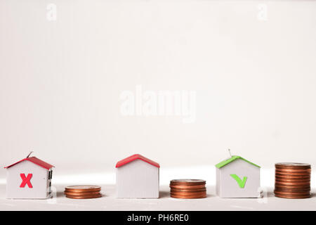 Mortgage and loan concept: Paper houses near coin piles to represent house value - Stock Image